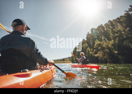 Image of senior couple canoeing in the lake on a sunny day. Kayakers in the lake paddling. - Stock Photo