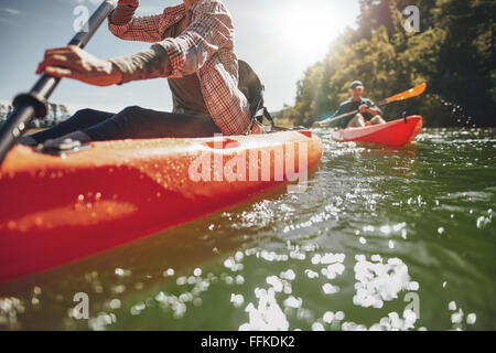 Cropped image of woman kayaking with a man in background. Couple canoeing in a lake on a summer day. - Stock Photo