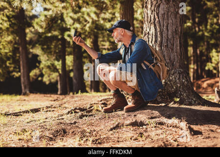 Mature man stops to check his position by using a compass while out on hike in the forest. male hiker sitting by - Stock Photo
