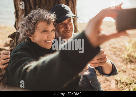 Happy senior couple taking their self portrait with their cell phone on camping day. Man and woman sitting together - Stock Photo