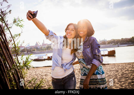 Woman and girlfriend taking a selfie with smartphone - Stock Photo