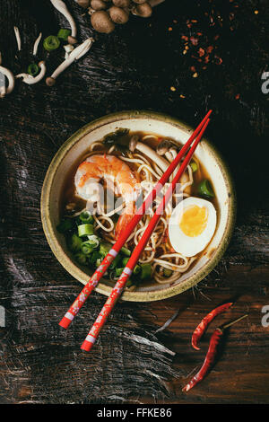 Ceramic bowl of asian ramen soup with shrimp, noodles, onion, sliced egg and mushrooms, served with red chopsticks - Stock Photo