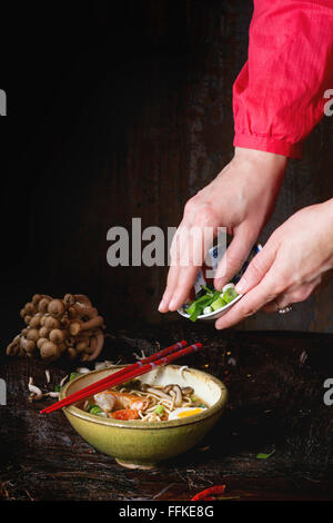 Female hand in red shirt sprinkle with sliced spring onion asian ramen soup with shrimp, noodles, sliced egg and - Stock Photo