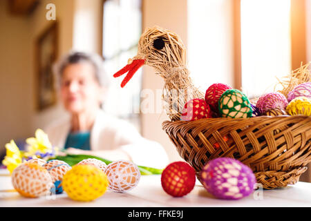 Basket with Easter eggs and hen in senior woman house - Stock Photo