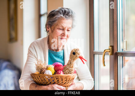 Woman holding basket with Easter eggs and straw hen - Stock Photo