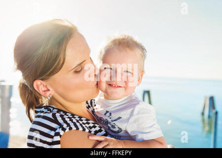 Mother kissing her boy, sunny summer by the water - Stock Photo