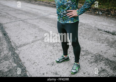 Lower body of fit runner with hands on hips - Stock Photo