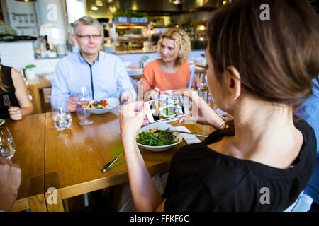Taking a picture of friends in restaurant - Stock Photo