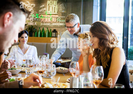 Group of friends on dinner party in restaurant - Stock Photo