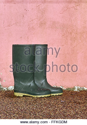 Dirty pair of green wellington boots against a pink painted wall - Stock Photo