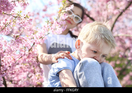 Keep your head up, it will be well!. Children sitting under a blooming tree, sister comforted by his brother - Stock Photo