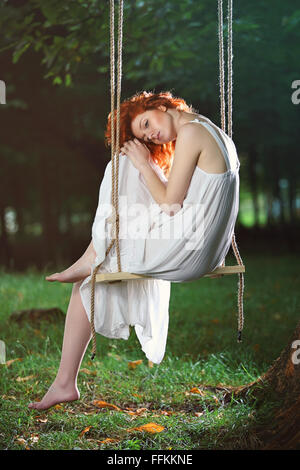 Beautiful sad woman on a swing in the forest . Romantic portrait - Stock Photo