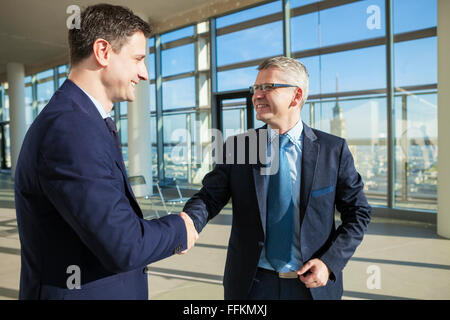 Two businessmen shaking hands in modern office - Stock Photo