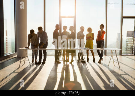 Team of architects in business meeting against urban skyline - Stock Photo
