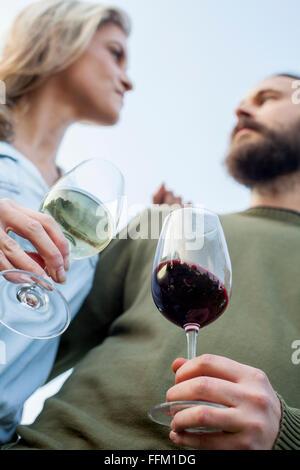 Heterosexual couple drinking wine in garden party - Stock Photo