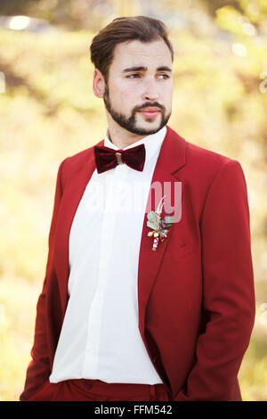 Portrait of the groom, red suit with a buttonhole flower. Wedding in style Marsala color. - Stock Photo