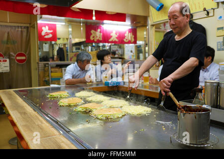 Chef cooking Hiroshima style okonomiyaki (Japanese savoury pancake) at Sarashina restaurant inside Okonomimura in - Stock Photo