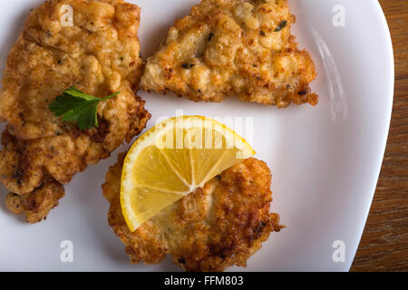 Schnitzel chop cutlet with lemon and parsley on a white plate - Stock Photo