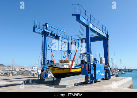 Mobile shipyard gantry crane moving a motorboat on to land, Corralejo Marina, Fuerteventura, Canary Islands, Spain - Stock Photo