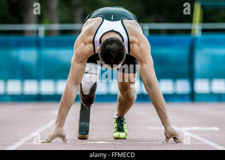 young athlete runner handicap start to sprint at stadium - Stock Photo