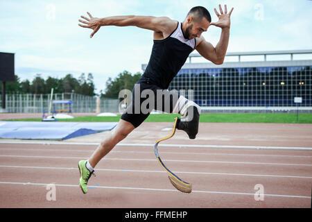 Explosive start of athlete with handicap at stadium - Stock Photo