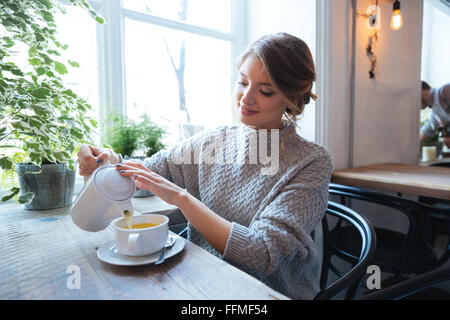 Happy woman drinking tea in cafe - Stock Photo