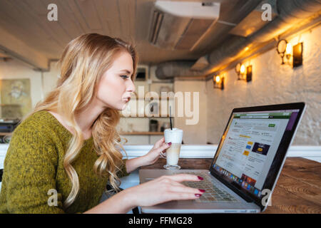Blonde woman using laptop computer in cafe - Stock Photo