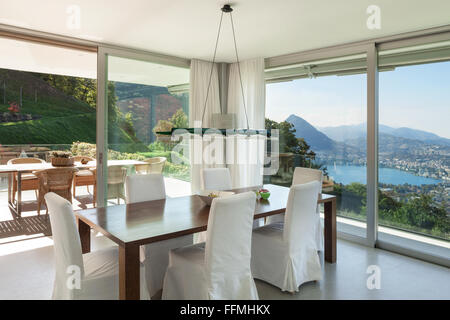 Modern dining room with wide windows, table set, spiral staircase ...