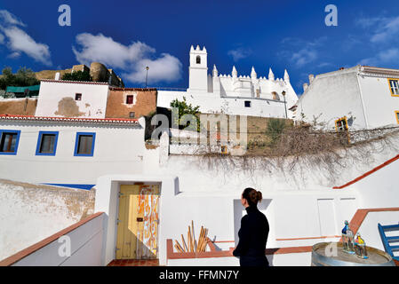 Portugal, Alentejo: Woman looking from terrace to church and castle of historic village Mértola - Stock Photo