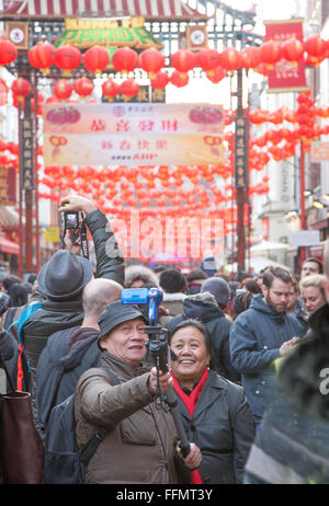Chinese couple take selfie at the Chinese New Year celebrations in Gerrard St London W1 - Stock Photo