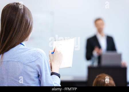Back view of young business woman writing and making notes in notepad sitting on public presetration in conference - Stock Photo