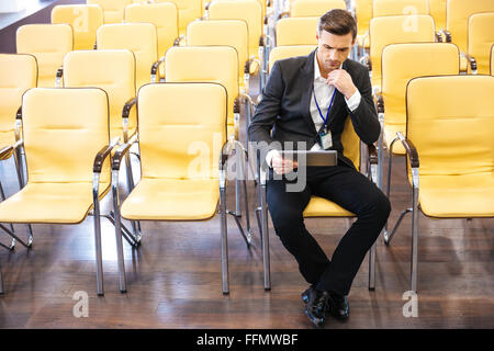 Concentrated businessman working with tablet in empty conference hall - Stock Photo
