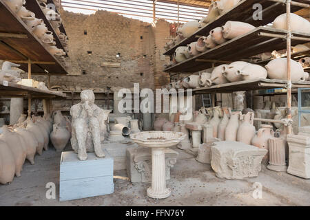 Earthenware pots and the cast of a person recovered from the ruins in Pompeii, Italy, Europe - Stock Photo