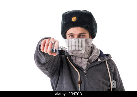 Man in winter hat and scarf threatening with gun.Studio shot. - Stock Photo