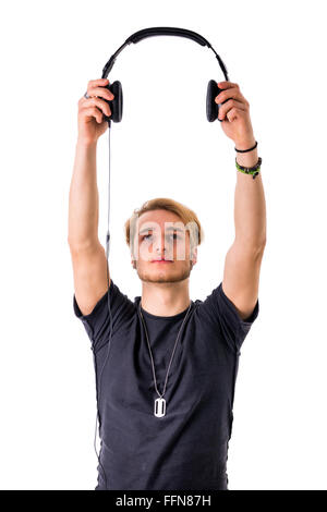 Blond man with beard holding headphones. Studio shot. - Stock Photo