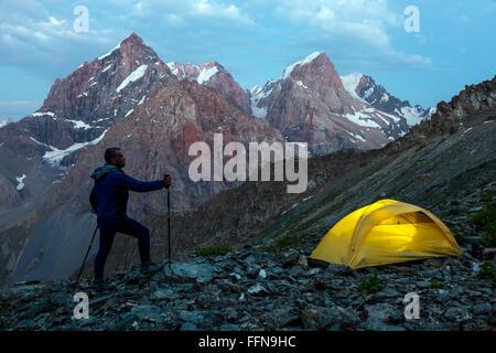Hiker walking toward illuminated climbing tent - Stock Photo
