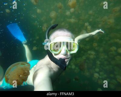 Jellyfish Lake, Palau Island, Pacific Ocean. Man swimming underwater, apnea free diving, snorkeling with video camera - Stock Photo