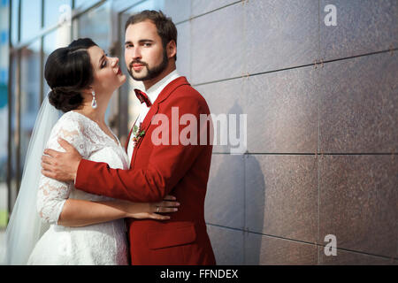Bride and groom, romantic wedding couple in a passionate outburst, near walls of building. - Stock Photo