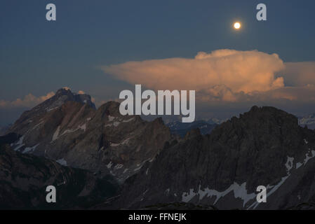 Full moon rising during the glowing sunset over Mount Drusenfluh and  Kirchlispitzen seen from Totalp mountain hut, - Stock Photo