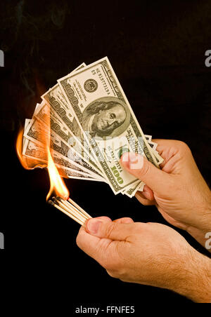 Money to Burn 1.  A man uses matches to set fire to a group of one hundred dollar bills. - Stock Photo
