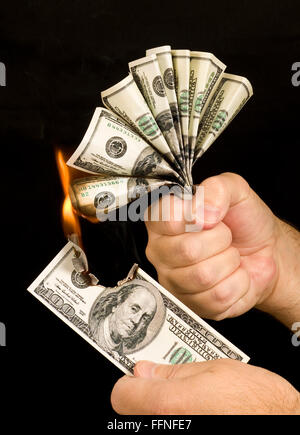 Money to Burn.  A man uses a one hundred dollar bill to set fire to the hand full of one hundred dollar bills in - Stock Photo
