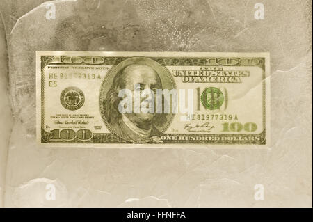 One Hundred Dollar Bill Frozen in Ice - Stock Photo