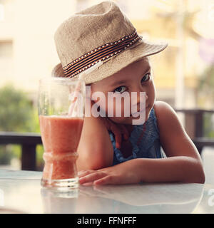 Alone unhappy kid girl sitting in restaurant and does not want to drink healthy juice on summer background