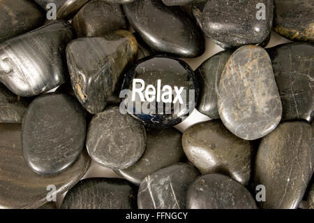 Relax Encouragement Stone on River Rocks - Stock Photo