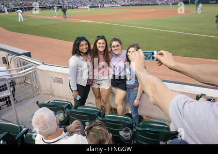 Four teenage women having their photo taken with a cell phone at Minnesota Twins baseball game. Minneapolis Minnesota - Stock Photo
