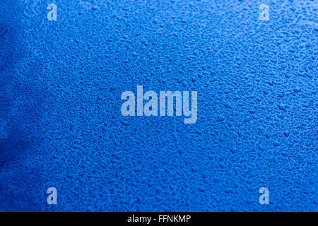 Waterdrops on blue car paint as underground, shallow focus - Stock Photo