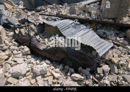 A crushed car under rubble of a building that collapsed after a 7.0 magnitude earthquake struck Haiti on 12 January - Stock Photo