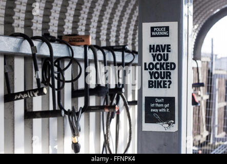 A 'Have you locked your bike?' sign warning about bike theft in front of bike locks locked around a bike shelter - Stock Photo