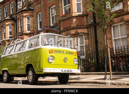 Old vintage green van parked in a street with Victorian houses in the background - Stock Photo