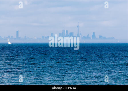 Toronto city skyline from across wavy blue rippled water with sailboat and other boats in distance in hazy fog. - Stock Photo